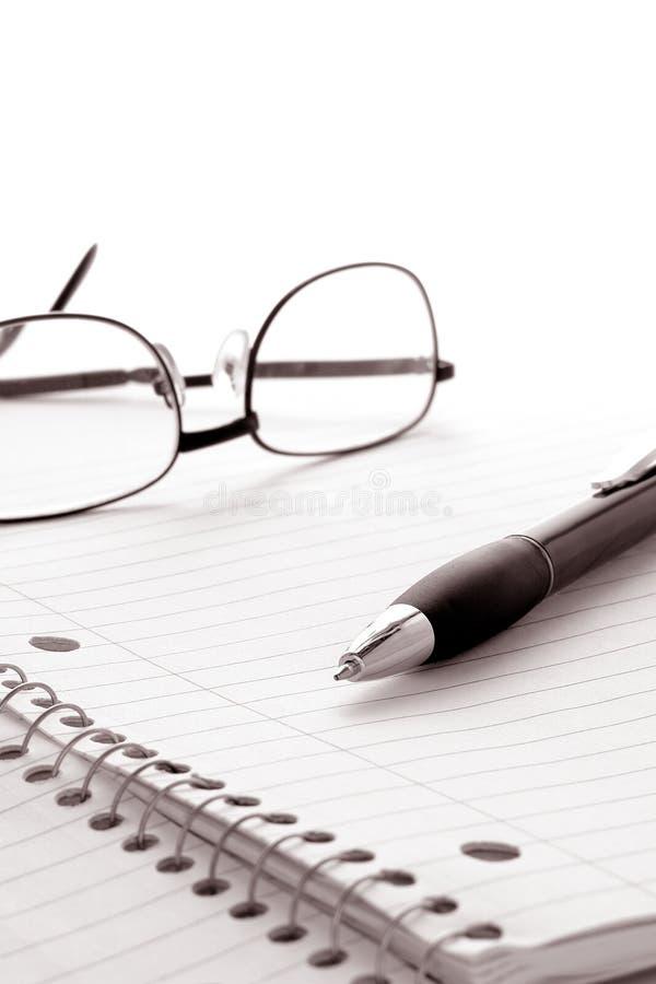 Feder und Gläser über Notizbuch-unbelegtes Papier-Blatt lizenzfreies stockfoto