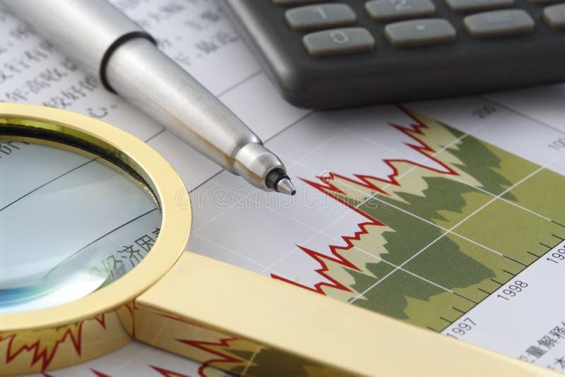 Feder, Vergrößerungsglas und Rechner auf Finanzberichten stockfotos