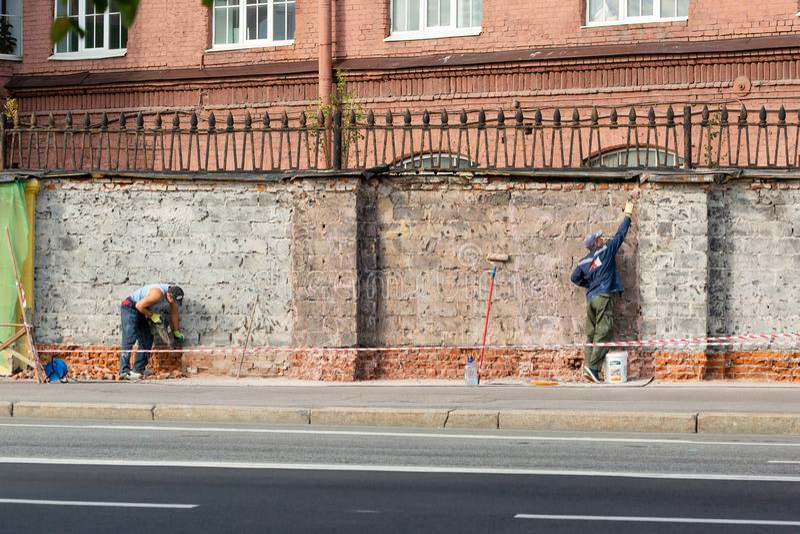 Federación rusa 16 de agosto de 2018: trabajadores que reparan una cerca del ladrillo alrededor del edificio imagen de archivo libre de regalías