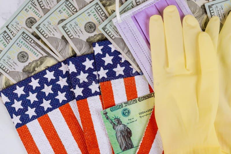 Federal monetary assistance stimulus U.S. economic tax return check USA dollar cash banknote on American flag Global pandemic. Global pandemic Covid 19 lockdown stock photo