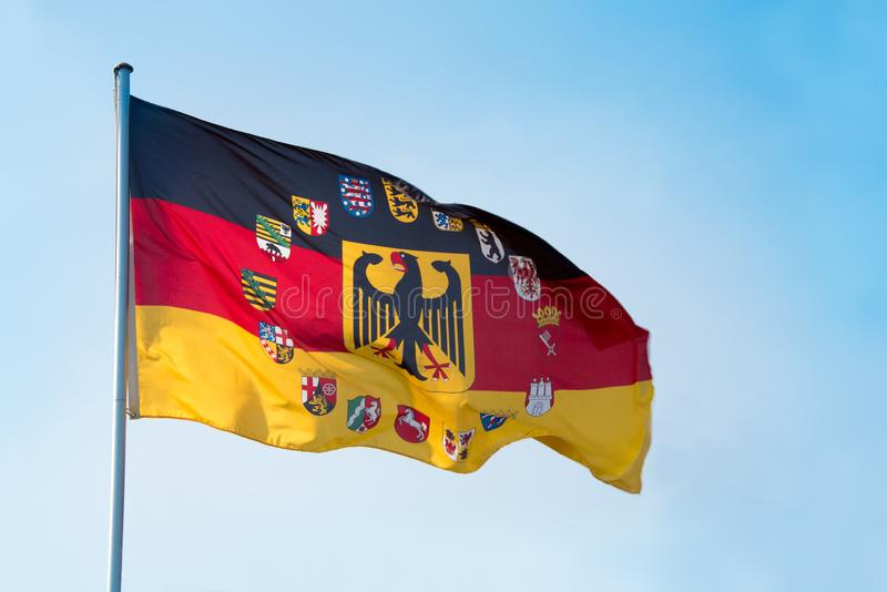 Federal republic of Germany flag with eagle and the crests, coat. Of arm of all states - with blue sky and copy space royalty free stock photography
