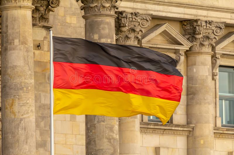 Federal Republic of Germany, German national flag. Waving in front of the Parliament building columns royalty free stock photo