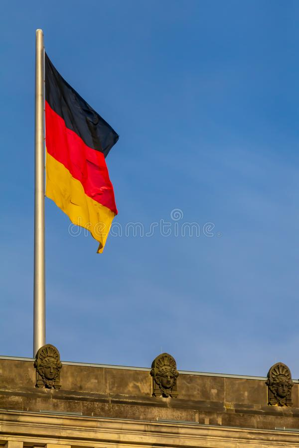 Federal Republic of Germany, German national flag. At the Parliament building waving on the blue sky background royalty free stock images