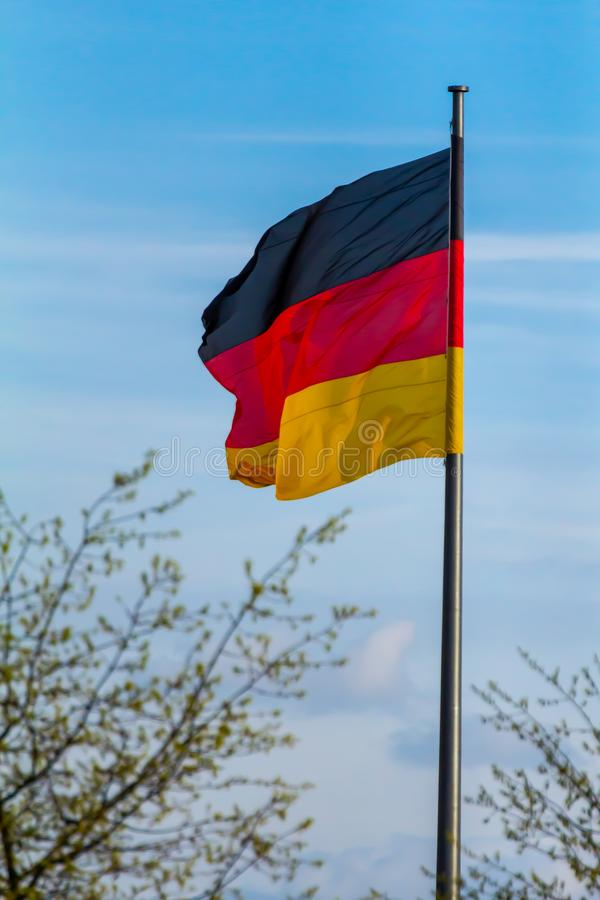 Federal Republic of Germany, German national flag. Waving on the blue sky background royalty free stock photo