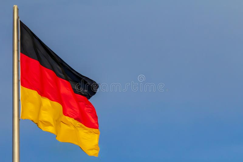 Federal Republic of Germany, German national flag. Waving on the blue sky background stock photography