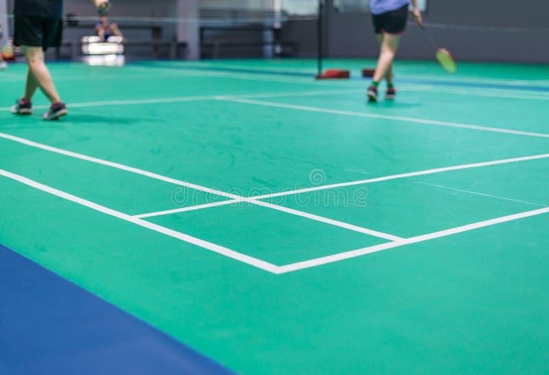 Federballplatz mit dem unscharfen Badmintonspieler, der Schläger ind hält stockfoto