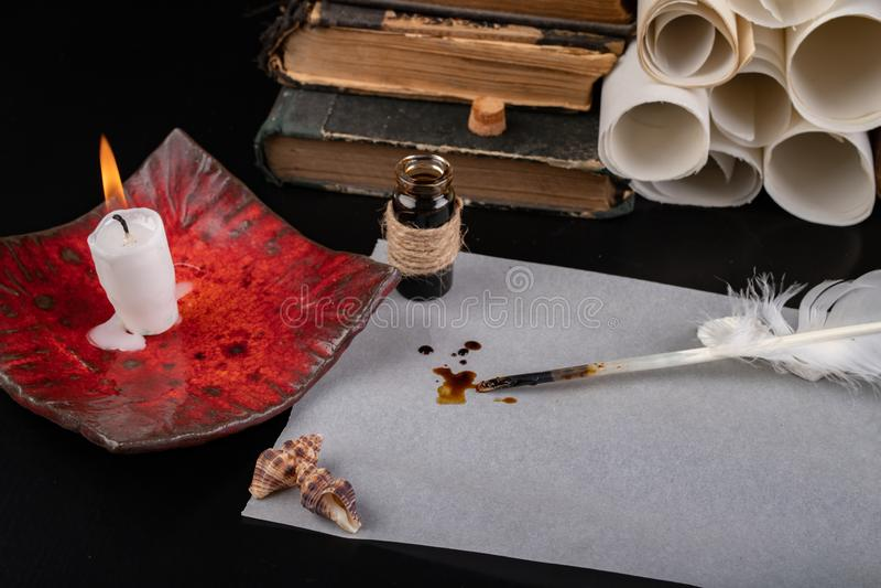 Federn von Vögeln für Schreiben und Kalligraphie auf altem Papier Ein Platz für einen alten Verfasser beleuchtet mit Kerzen lizenzfreie stockfotos
