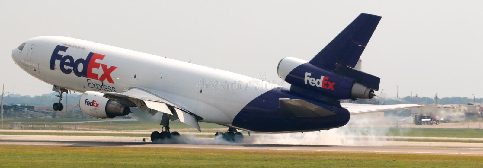A FedEx Airplane touches down at the airport. stock photo