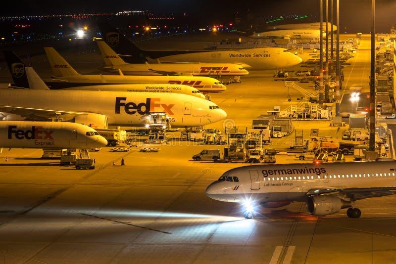 Fedex en germanwingsvliegtuigen bij luchthaven Keulen Bonn Duitsland bij nacht stock afbeelding