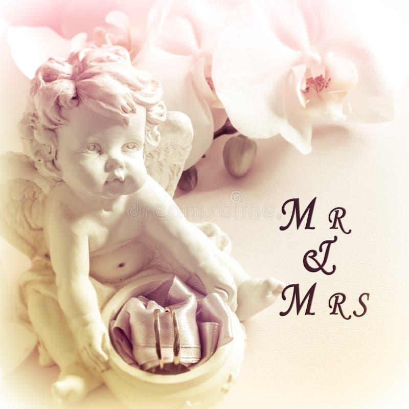 Fedi nuziali bianche della scultura di angelo dell'orchidea su fondo rosa e sig fotografie stock