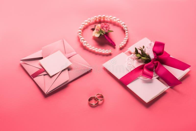 fedi nuziali, collana della perla, boutonniere e buste rosa con gli inviti fotografie stock libere da diritti