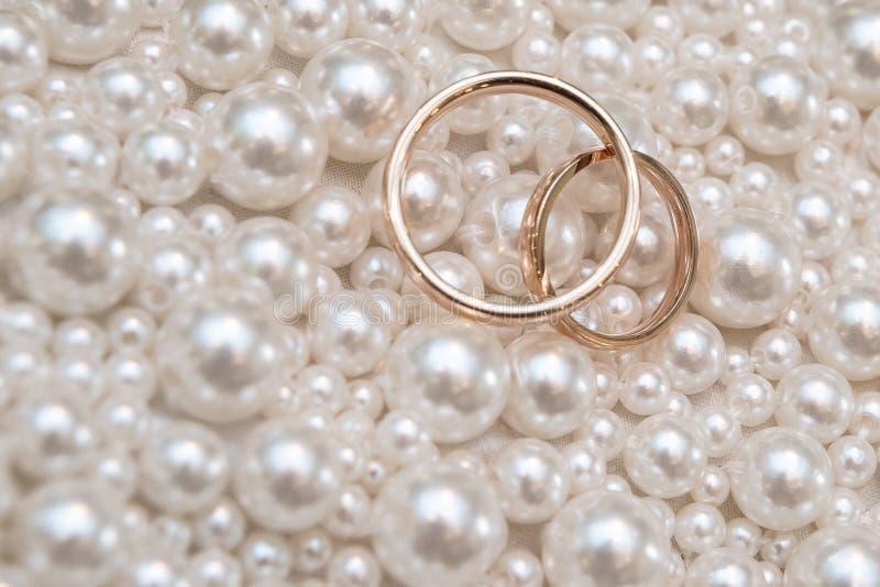 Fedi nuziali con il fondo della collana della perla per nozze o il concetto di giorni di biglietti di S. Valentino : Stile d'anna fotografia stock libera da diritti