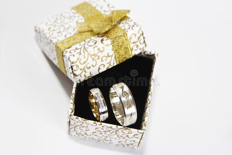 Fedi nuziali dell'argento dell'oro in un contenitore di regalo su un fondo nero fotografie stock libere da diritti