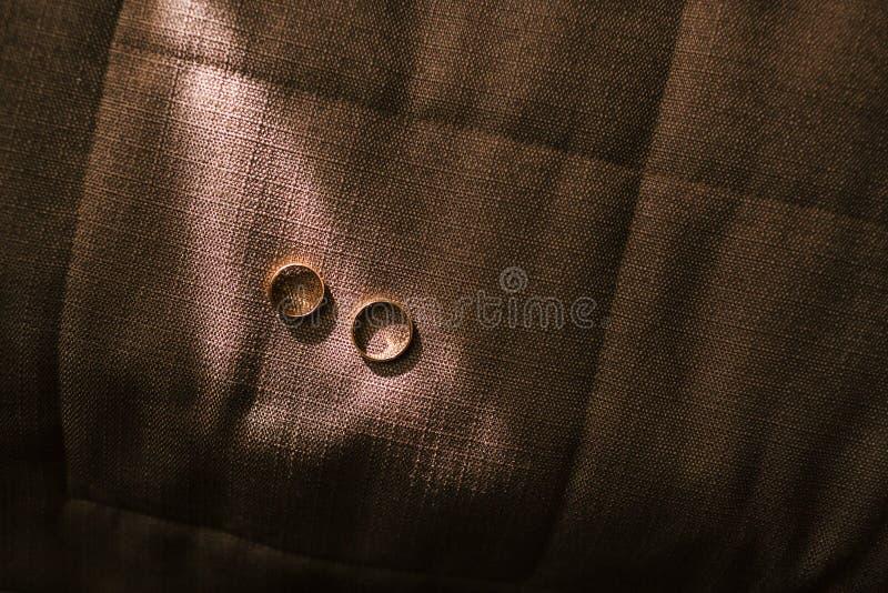 Fedi nuziali dorate che pongono al sole su un fondo scuro del tessuto Foto insolita dei gioielli nozze illustrazione fotografia stock