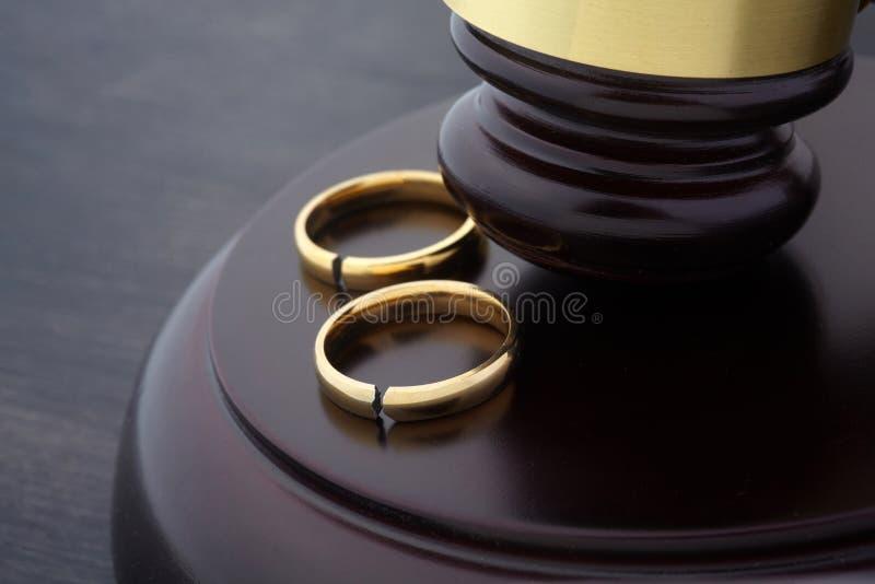 Fedi nuziali dorate con un martelletto del giudice e della crepa, primo piano immagini stock