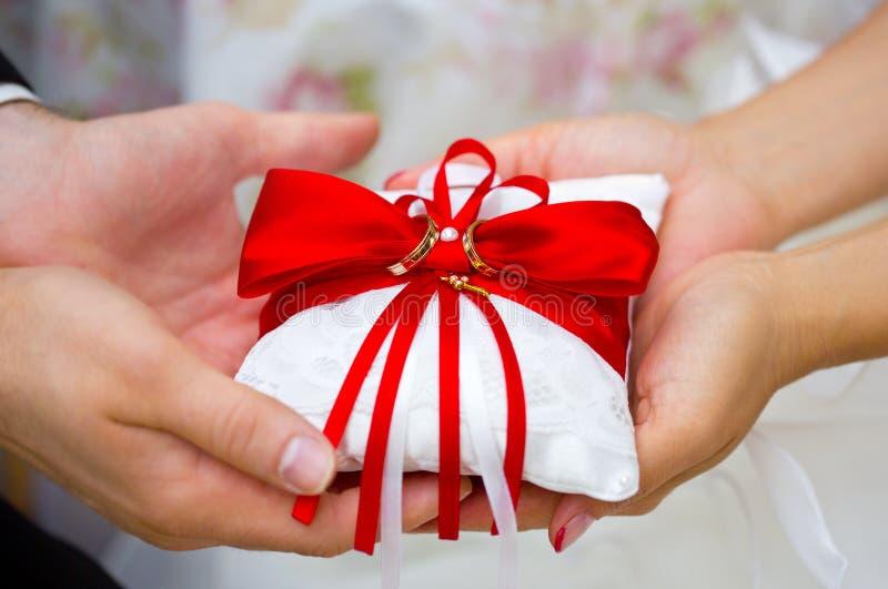 Fedi nuziali dorate sul cuscino rosso e bianco dell'anello in mani della sposa e dello sposo immagini stock