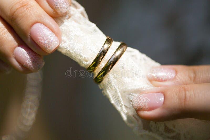 Fedi nuziali dorate sul velo bianco del pizzo in dita della sposa fotografie stock libere da diritti
