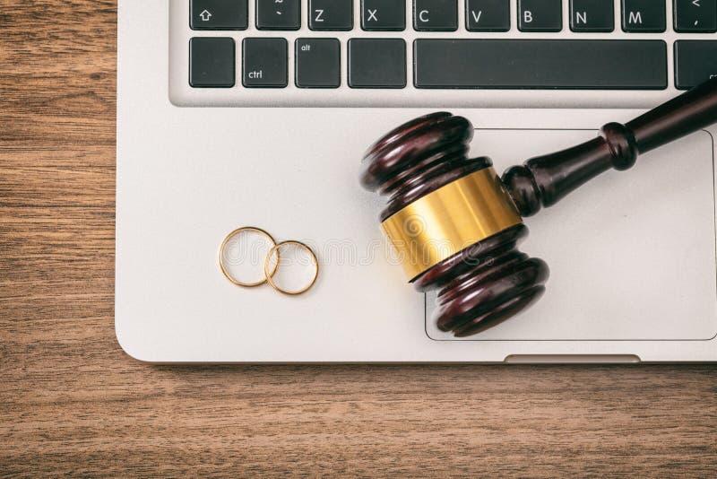 Fedi nuziali e martelletto del giudice sul computer portatile del computer, fondo di legno, visualizzazione superiore fotografia stock libera da diritti