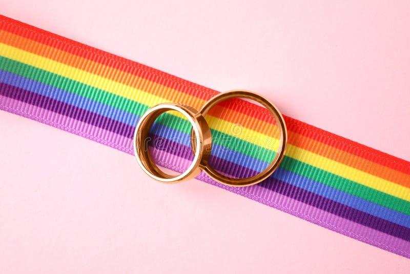 Fedi nuziali e nastro dell'arcobaleno sul fondo di colore, vista superiore fotografie stock