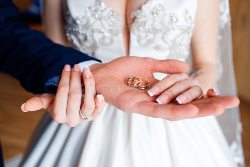 Fedi nuziali nelle mani della sposa e dello sposo fotografia stock libera da diritti