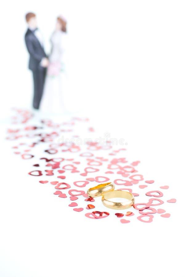 Fedi nuziali pure dell'oro con i cuori rossi ornamento e sposa e g fotografia stock libera da diritti