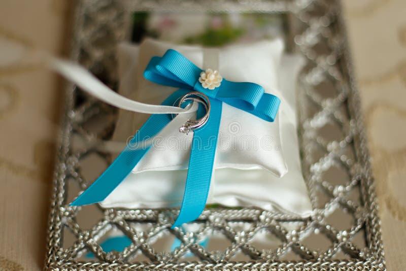 Fedi nuziali su un cuscino con il nastro blu immagini stock