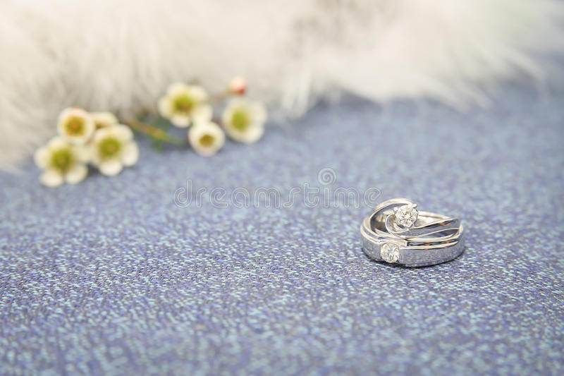 Fedi nuziali sul sofà di lusso con i bei fiori fotografia stock