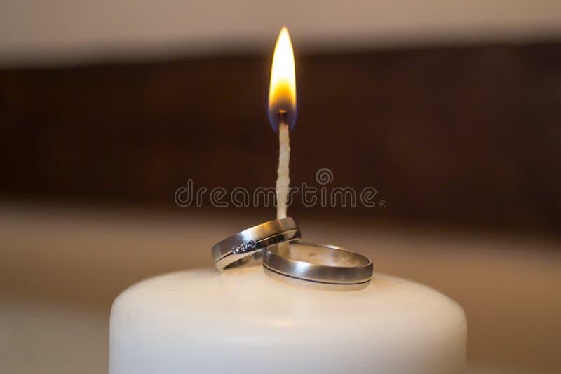 Fedi nuziali sulla candela in fuoco fotografie stock