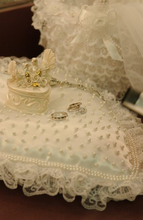 Fedi nuziali sulle fedi nuziali bianche dell'oro del cuscino del cuore su bianco immagine stock