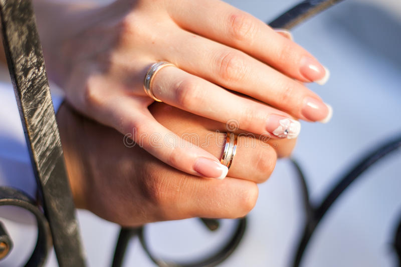 Fedi nuziali sulle mani delle persone appena sposate immagini stock