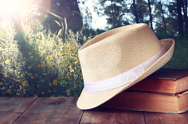 Fedora hat and stack of books over wooden table and evening nature country side background. relaxation or vacation concept stock images
