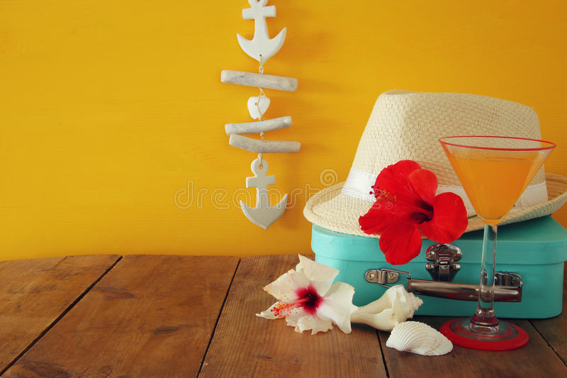 Fedora hat, tropical hibiscus flower on wooden table. relaxation or vacation concept stock images