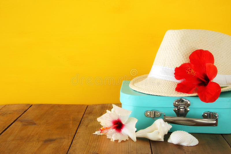 Fedora hat, tropical hibiscus flower on wooden table. relaxation or vacation concept stock photo
