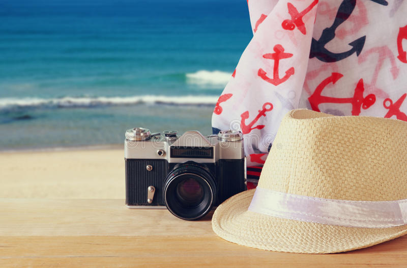 Fedora-Hut, alte Weinlesekamera und Schal über Holztisch und Meer gestalten Hintergrund landschaftlich Entspannungs- oder Ferienk lizenzfreies stockbild