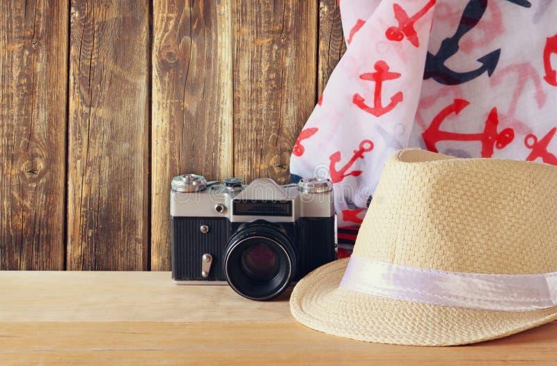 Fedora-Hut, Schal und alte Weinlesekamera über Holztisch Entspannungs- oder Ferienkonzept stockbild