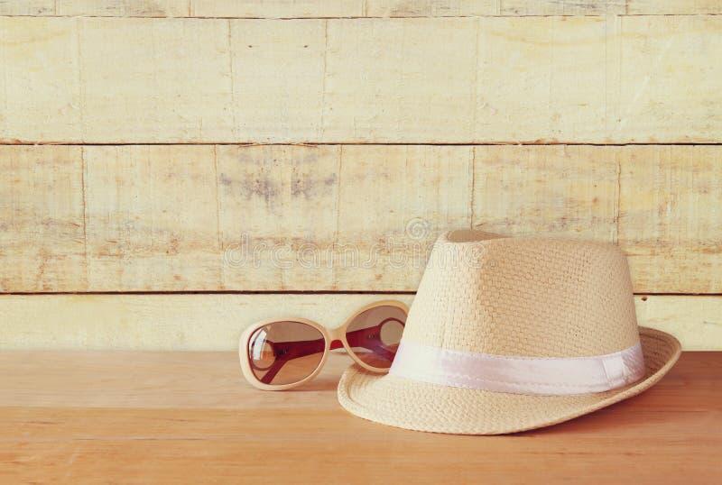 Fedora-Hut und -Sonnenbrille über Holztisch Entspannungs- oder Ferienkonzept stockfotografie
