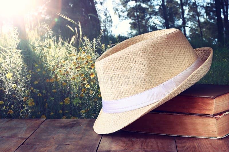 Fedora-Hut und Stapel Bücher über Holztisch- und Abendnaturlandseitenhintergrund Entspannungs- oder Ferienkonzept stockbilder