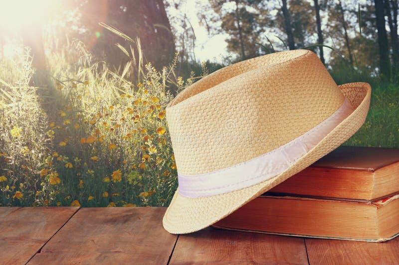 Fedora-Hut und Stapel Bücher über Holztisch- und Abendnaturlandseitenhintergrund Entspannungs- oder Ferienkonzept lizenzfreie stockfotografie