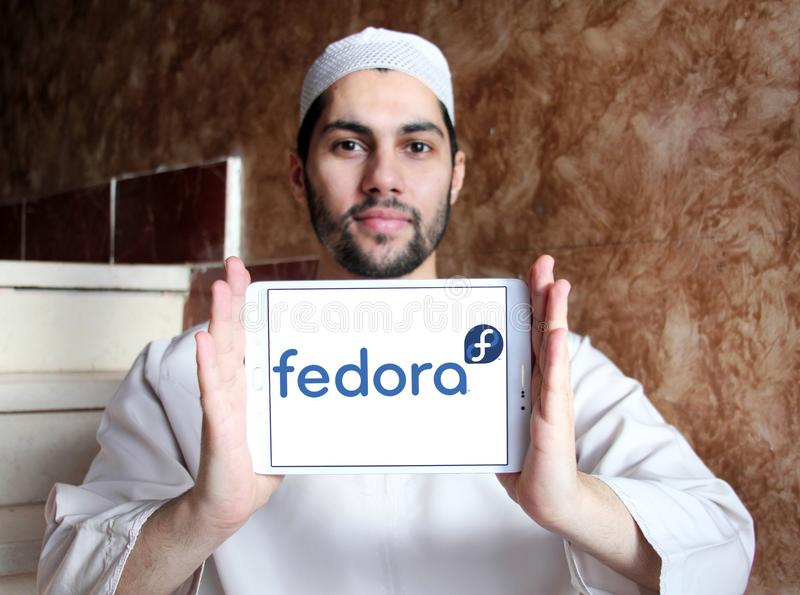 Fedora operating system logo. Logo of Fedora operating system on samsung tablet holded by arab muslim man. Fedora is a Linux distribution developed by Fedora royalty free stock images