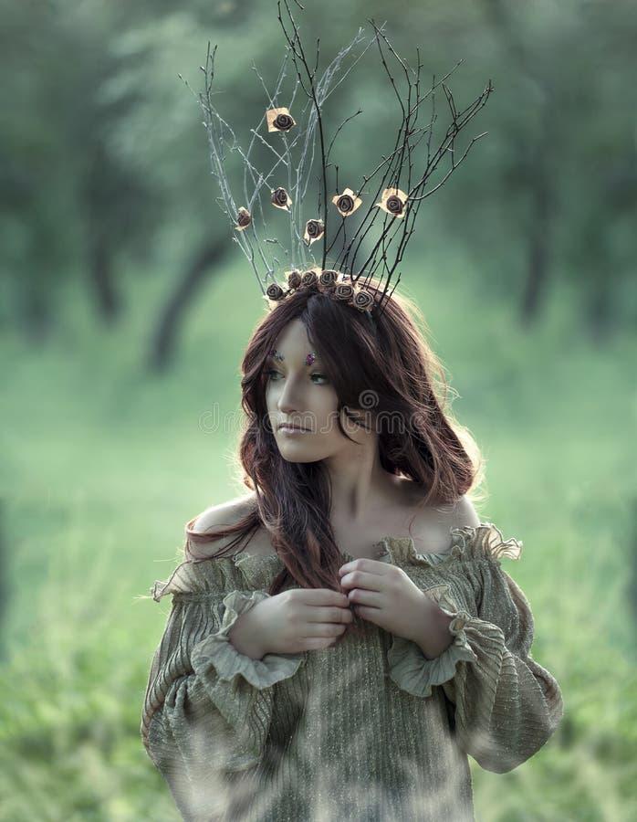 Fee-staart bosnimf die kroon, mooie sexy vrouw bij de lentetuin dragen, uitstekende dromerige manierstijl stock foto's