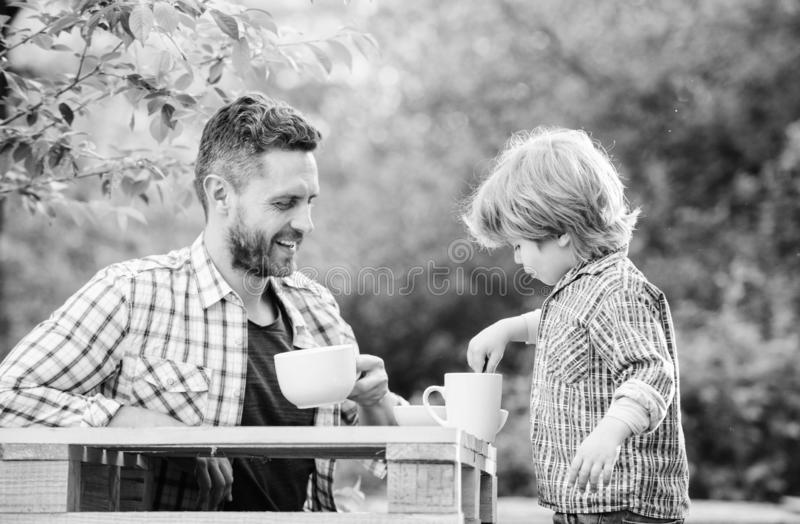 Feed in right way for childs stage of development. Feed son solids. Feed your baby. Natural nutrition concept. Dad and. Cute toddler boy having lunch outdoors stock photography