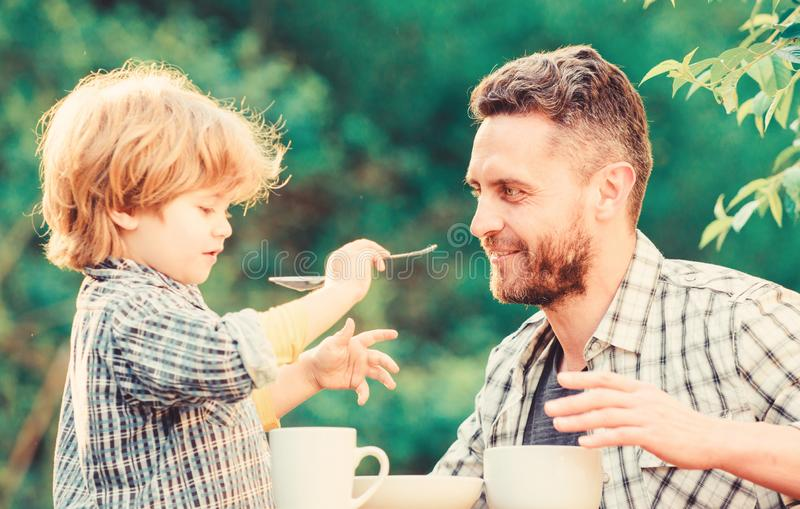 Feed son solids. Dad and boy eat and feed each other outdoors. Ways to develop healthy eating habits. Feed your baby royalty free stock image