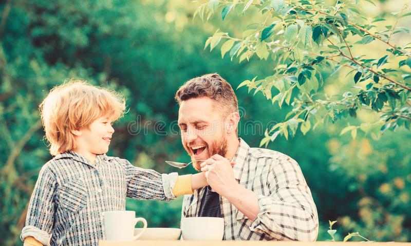 Feed son solids. Feed your baby. Natural nutrition concept. Dad and cute toddler boy having lunch outdoors. Child care royalty free stock photography
