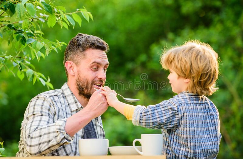 Feed your baby. Natural nutrition concept. Feeding son natural foods. Stage of development. Feed son solids. Dad and boy stock photo