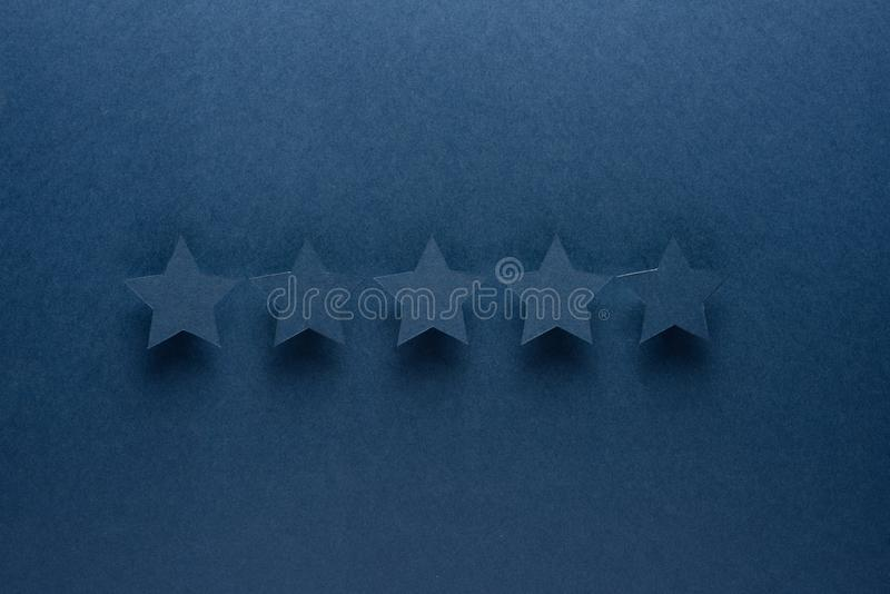 Feedback concept. Five blue paper stars of approval on a blue background. stock photos