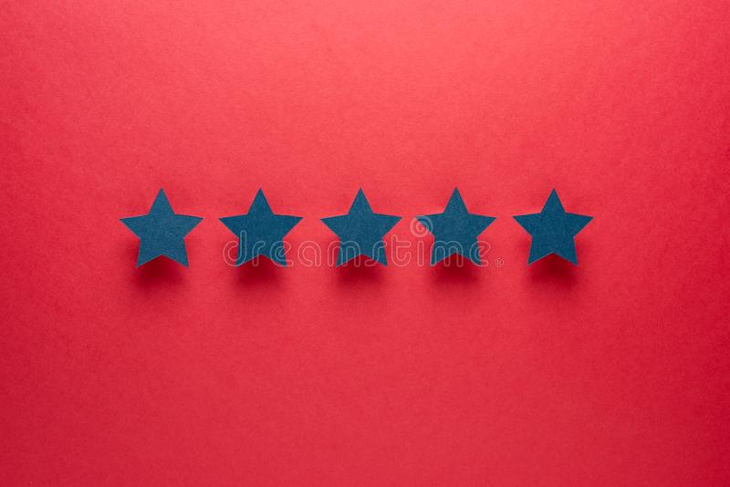 Feedback concept. Five blue paper stars of approval on a red background. stock photo