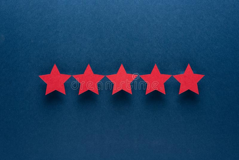 Feedback concept. Five red paper stars of approval on a blue background. stock photos
