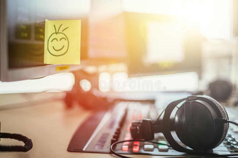 Feedback and motivation concept: Smiley Illustration at the working place, radio studio. Smiley illustration at a radio studio, metaphor for feedback and royalty free stock photo