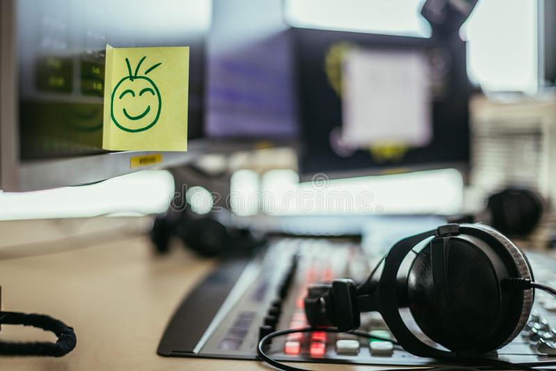 Feedback and motivation concept: Smiley Illustration at the working place, radio studio. Smiley illustration at a radio studio, metaphor for feedback and stock image