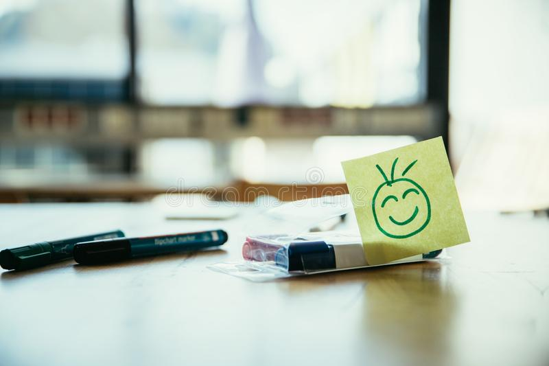 Feedback, motivation and workshop concept: Smiley Illustration on a working place, pens and window in the background. Smiley illustration at the working place royalty free stock photo